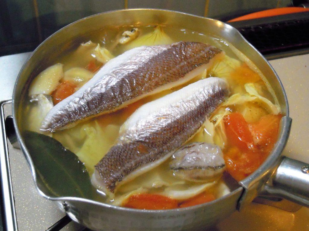 ブイヤベースのスープに野菜とホウボウの身を入れる
